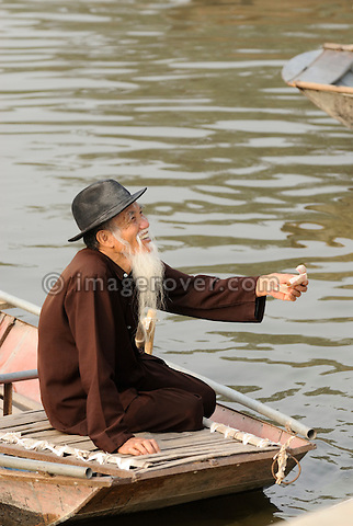 Asia, Vietnam, Tam Coc near Ninh Binh. Elderly vietnamese boat man at Tam Coc (Three Caves) receiving the trip fare. To visit the Three Caves (Tam Coc) tourists are punted in metal boats along the watery landscape and through three long caves. At some places these are so low that peope have to duck, while boat people propel the boat by pushing on the cave roof with their hands.