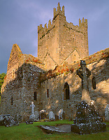 County Kilkenny, Ireland<br /> Cemetery headstones border the outer stone walls and church tower of Jerpoint Cistercian Abbey (11th-15th centuries)