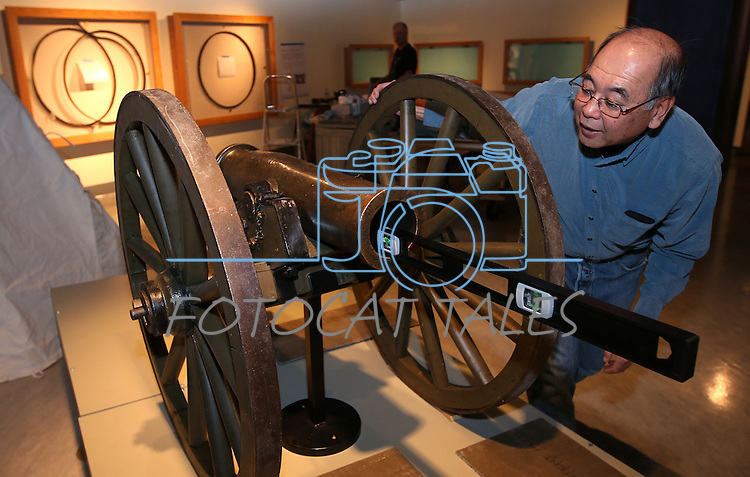 "Nevada State Museum Archaeologist Gene Hattori checks a level while setting up the Fremont Cannon as part of the ""Finding Fremont: Pathfinder of the West"" exhibit at the museum in Carson City, Nev., on Monday, Jan. 27, 2014. (Las Vegas Review-Journal/Cathleen Allison)"