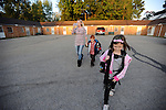 Amanda takes two of her children to the bus stop early one morning. Brant, age 6, holds Amanda's hand as Brittni, age 7, leads the way.