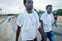 Profughi eritrei si recano nell'hangar dell'aeroporto di lampedusa per la cerimonia in onore dei compagni morti nel naufragio del barcone con il quale hanno cercato di raggiungere le coste dell'isola. Immigrants walk to attend a ceremony for some of the African migrants killed in a shipwreck off the Italian coast at the Lampedusa airport.