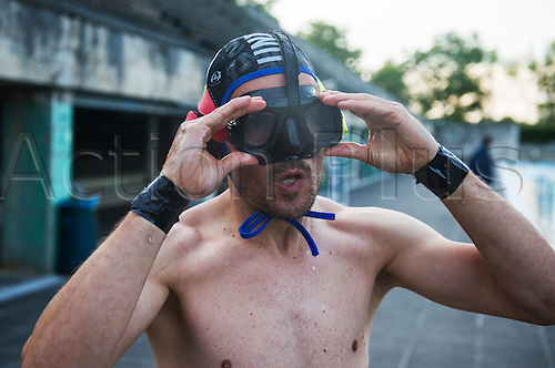 29.07.2015. Berlin, Germany.  Wolfgang Tress puts on his swim googles prior to playing underwater rugby in the public swimming pool at the Olympic stadium in Berlin, Germany. The players try to score by placing the ball, filled with salt water, into the basket of the opposing team.