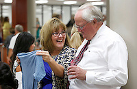 NWA Democrat-Gazette/DAVID GOTTSCHALK  Cynthia Voss, of Shaw Elementary School, displays a shirt with the school district mission statement All Means All to Jim Rollins, superintendent of the Springdale School District, during the annual appreciation breakfast at Springdale High School Monday, August 10, 2015. The teachers received items from vendors, ate breakfast and participated in a welcoming program.