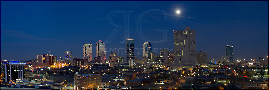 The nearly full moon rises over the city of Fort Worth, Texas in this nigthtime panorama of cowtown, USA.