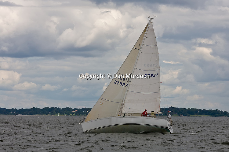racing sailboat on port tack under a cloudy sky