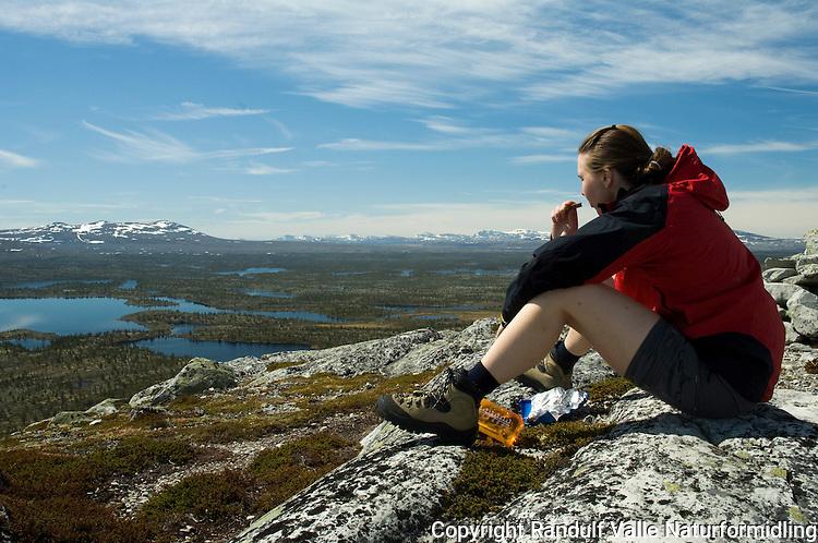 Jente tar matpause på Bustvålen ved Rogen. Utsikt inn i Femundsmarka --- Girl having lunch in Rogen area