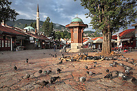 The Sebilj, a public fountain in Ottoman style made from wood on a stone base, built 1891, in Bascarsija Square, Sarajevo, Bosnia and Herzegovina. Behind is the 16th century Gazi Husrev-beg Mosque. The square is also called Pigeon Square as people sit in the cafes drinking coffee and feeding the many pigeons which congregate here. The city was founded by the Ottomans in 1461. Picture by Manuel Cohen