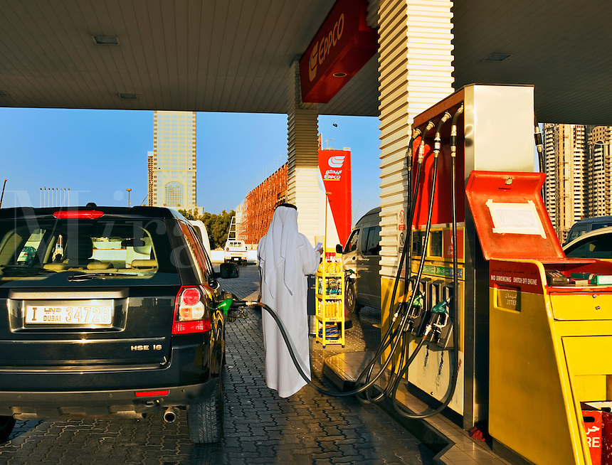 Dubai.  Arab man filling his car at petrol station in the city.