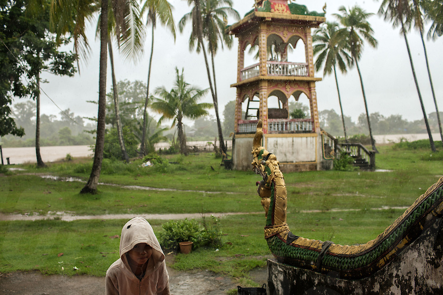 August 03, 2013. Don Sahong (Laos). A kid plays in the rain in courtyard of Don Khon's pagoda. © Thomas Cristofoletti / Ruom