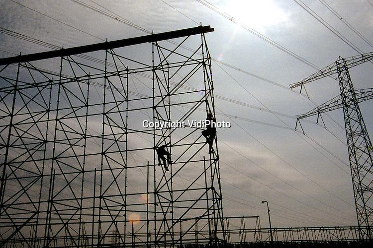 Foto: VidiPhoto..VALBURG - Langs de A50, ter hoogte van knooppunt Valburg, worden voorbereidingen getroffen voor het verplaatsen van zeven hoogspanningsmasten. De stroompalen moeten zo'n 25 meter verschoven worden voor de Betuwelijn. De hoogspanningslijnen lopen over het verkeersknoooppunt Valburg (A50/A15). Om te voorkomen dat er troep op het verkeer terechtkomt, wordt er op dit moment aan beide zijden van het viaduct een stalen constructie gebouwd. Daartussen wordt komende weken een vangnet gehangen.