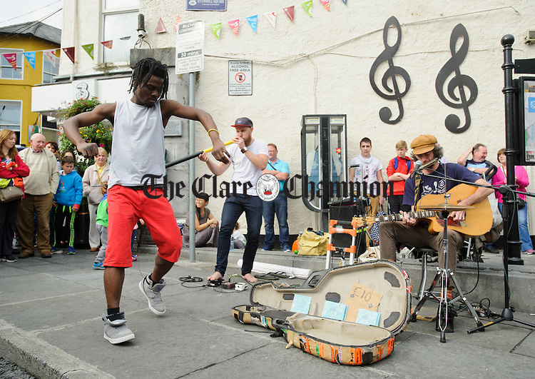 A passer by dances the music of buskers in O Connell square, Ennis during Fleadh Cheoil na hEireann. Photograph by John Kelly.