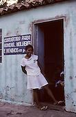 Conceicao do Araguaia, Brazil. 'Costureira para Homens, Mulheres e Meninos em Geral'; clothes maker; smiling woman outside a small house. Para State.