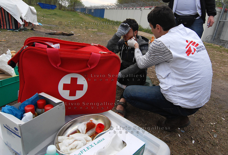 Subotica / Serbia  160416<br /> Dr. Vladimir Andric, MSF chief of the Mobile Clinic, treats a refugee wounded in the face.<br /> In the back-ground the Wall and barbed wire that separates Serbia from Hungary.<br /> Photo Livio Senigalliesi