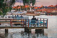 Ett par njuter på en bänk en sommarkväll vid Riddarfjärden i Stockholm. / A couple on a bench enjoying a summer evening at Mälaren in Stockholm Sweden.