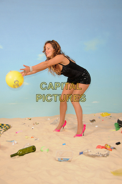 JADE JAGGER.The launch of the Corona Save The Beach project, Trafalgar Hotel, London, England.June 23rd, 2009.full length black shorts top swimsuit sequins sequined ball yellow sand rubbish garbage silver bracelet pink neon fluorescent shoes throwing bending leaning funny gesture .CAP/CAS.©Bob Cass/Capital Pictures.