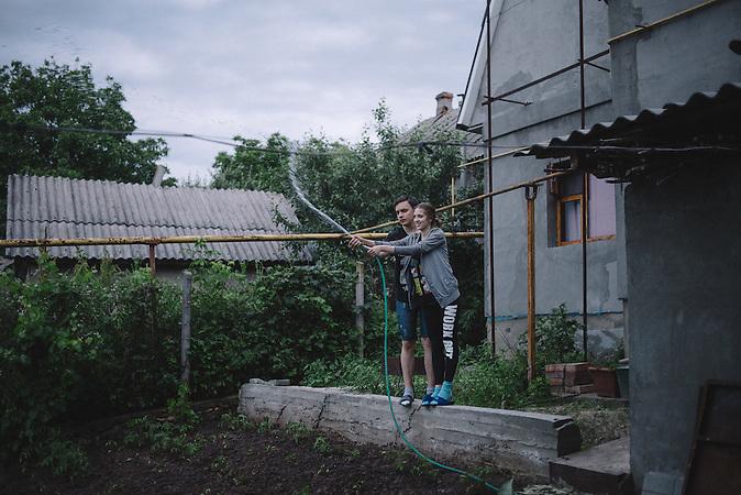 Katrine and Alexander watering garden together. Ribnita, Transnistria