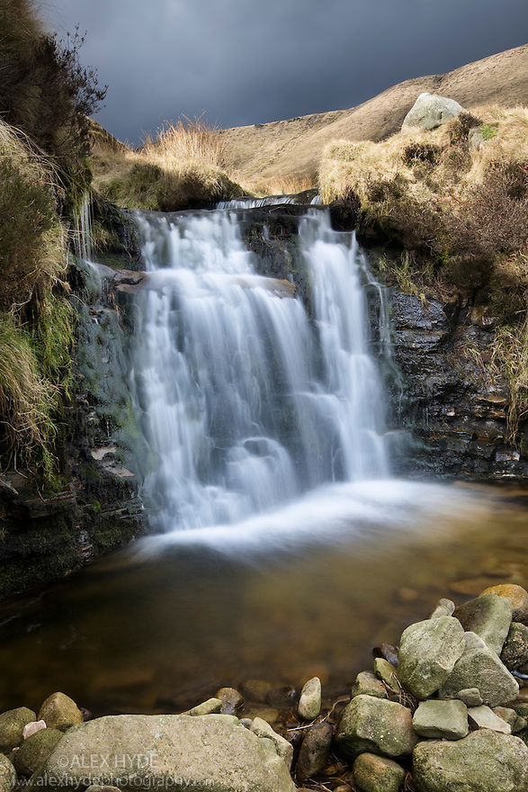 Waterfall flowing over gritstone, Kinder Scout, Peak District National Park, Derbyshire, UK. February.