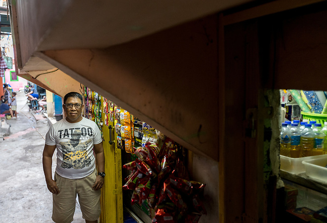 13 August 2019, Jakarta, Indonesia: Small shop owner Mohammad Saleh (53) stands outside his shop in Waduk Pluit. He claims it was 4 metres high when he first built it but now the land has sunk so much he can nearly touch the top with his head. He was with residents speaking about the lack of water facilities that the local poor population has access to. Water is hauled in each day by motorcycle and trucks and by hand to allow residents of the kampungs to  buy it for washing and to do laundry. Separate water is needed for drinking. The Jakarta Governor is proposing a program to send in trucks of water for the locals to get for free. They are living in villages below the seawater line on the coast of Jakarta that is sinking faster than anywhere else in the world so they have the position of being surrounded by water yet not having access to clean supplies. Picture by Graham Crouch/The Australian