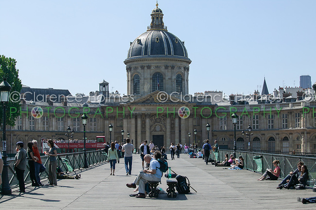People walk and relax on Le Pont des Arts with the Collège des Quatre-Nations (College of Four Nations) in the background.