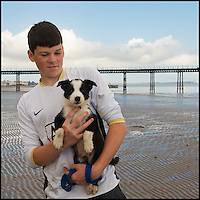 Boy holding a puppy on the beach, Ramsey, Isle of Man
