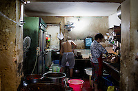 Kitchen workers prepare food and dishes for restaurant patrons at Gang Shan Zha Zha, a popular streetside hotpot restaurant on Tiyu Road in central Yuzhong distrist, Chongqing, China.<br /> <br /> The restaurant sits on the site of a former neighborhood garbage collection point and &quot;zha zha&quot; is local slang for &quot;garbage.&quot; The restaurant has been open for 5 years and recently opened a second location elsewhere in Chongqing. A manager of the restaurant said that they server 60-70 tables every night, with many tables' bills coming to over 1000RMB. The restaurant often has a long wait. The site is well-reviewed on online restaurant sites similar to Yelp and is known for having good flavor, serving fresh food, and being clean.