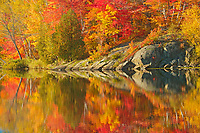 Autumn colors  and Precambrian Shield rock reflected in Simon Lake<br />