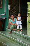 A woman and a little girl enjoy the fresh morning air on the steps of a country house in the Mekong Delta near My Tho, Vietnam. Oct. 30, 2011.