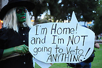 Phoenix, Arizona (February 25, 2014) - A demonstrator dressed as a witch holds a sign expressing her opinion on a possible veto to the SB 1062 bill. Arizona's Senate Bill 1062 is galvanizing the LGBT community and other civil and religious groups in the state. A crowd rallied in front of Arizona's Capitol in Phoenix to continue pressuring governor Jan Brewer to veto what they call a discriminatory bill. If approved, SB1062 would amend the existing Religious Freedom Restoration Act, which will allow business owners to deny service to gay and lesbian customers so long as proprietors were acting solely on their religious beliefs. As of this protest, the SB1062 is on Brewer's desk awaiting her approval or veto. Photo by Eduardo Barraza © 2014