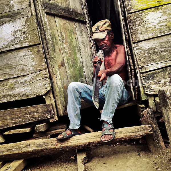 A Panamanian peasant checks the sharpness of the machete blade while sitting in the door of his house in Boca de Cupe, a community in the jungle region of Darién, Panama, 27 January 2015.