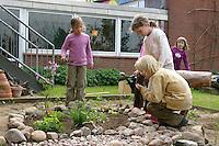Schulgarten, Anlage eines Schmetterlingsgarten, Garten der Grundschule Nusse wird als Projektarbeit von einer 1. Klasse gestaltet, Beete werden in Form eines Schmetterlings angelegt und mit für Nektarliebende Falter wichtigen Blumen bepflanzt, Kinder arbeiten an den Beeten, Gartenarbeit