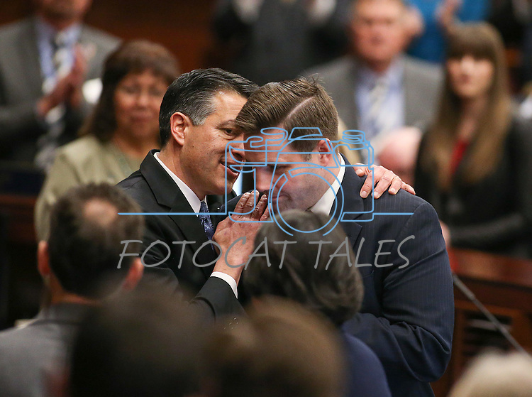 Gov. Brian Sandoval stops for a quick word with Director of Military and Veterans Policy Caleb Cage following his State of the State address at the Legislative Building in Carson City, Nev., on Thursday night, Jan. 15, 2015. (Las Vegas Review-Journal/Cathleen Allison)