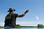 Pará State, Brazil. Xingu River. Boatman Paulo Juruna fishing.