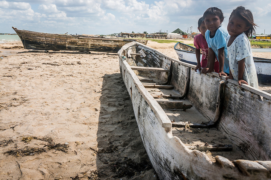 Children posing with an old dugout canoe and fishing boat on the beach at Manaure, La Guajira, Colombia.