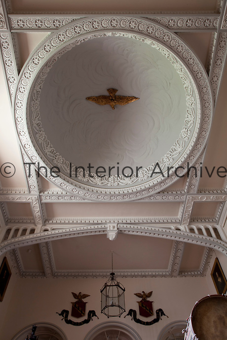 The impressive domed ceiling of the staircase hall, its coffered mouldings adorned with stucco medallions and a central relief reminiscent of clouds
