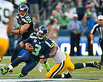 Seattle Seahawks quarterback Russell Wilson (3) slides down while being chased by Green Bay Packers defensive end Datone Jones (95)  in the NFL Kickoff held at CenturyLink Field September 4, 2014 in Seattle. Casey was flagged on the play. Wilson completed 19 passes for 191 yards, rushed for 29 yards as The Seahawks beat the Packers 36-16.   ©2014.  Jim Bryant Photo. ALL RIGHTS RESERVED.