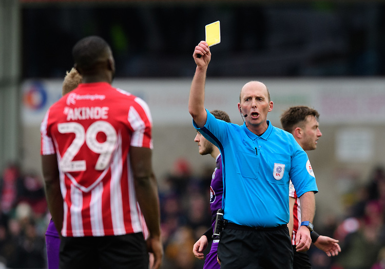 Lincoln City's John Akinde is shown a yellow card by referee Mike Dean<br /> <br /> Photographer Chris Vaughan/CameraSport<br /> <br /> The EFL Sky Bet League Two - Lincoln City v Grimsby Town - Saturday 19 January 2019 - Sincil Bank - Lincoln<br /> <br /> World Copyright © 2019 CameraSport. All rights reserved. 43 Linden Ave. Countesthorpe. Leicester. England. LE8 5PG - Tel: +44 (0) 116 277 4147 - admin@camerasport.com - www.camerasport.com