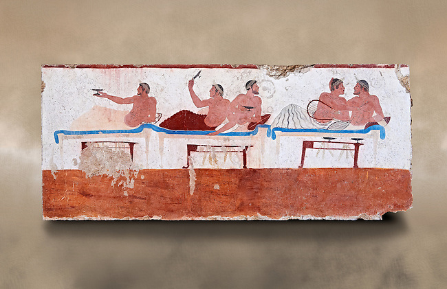 """Greek Fresco on the inside of Tomb of  the Diver  [La Tomba del Truffatore]. This panel is from one of the long sides of the tomb and shows a symposium of men lying on couches facing low tables on which goblets have been placed.  The abondon experienced at the Synposium was one way in which the dead could access the next world . The tomb is painted with the true fresco technique and its importance lies in being """"the only example of Greek painting with figured scenes dating from the Orientalizing, Archaic, or Classical periods to survive in its entirety. Paestrum, Andriuolo.  (480-470 BC  )"""