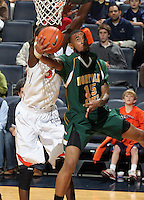Dec. 20, 2010; Charlottesville, VA, USA; Norfolk State Spartans guard/forward Rodney McCauley (15) floats under the basket in front of Virginia Cavaliers center Assane Sene (5) during the game at the John Paul Jones Arena. Virginia won 50-49. Mandatory Credit: Andrew Shurtleff
