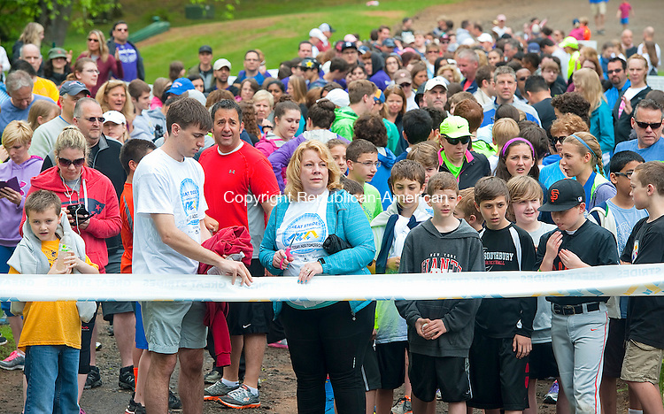 SOUTHBURY, CT--051615JS04- Michael DiMaio, left, and Kris DiMaio, the son and wife of the late Dr. Tony DiMaio, cut the ribbon to officially start the 5th annual Great Strides Walk for Cystic Fibrosis Saturday at Ballantine Park in Southbury. More than 400 participants too part in the event which was dedicated  to Dr. Dimaio who passed away in Janurary from Cystic Fibrosis at the age of 52. <br />  Jim Shannon Republican-American
