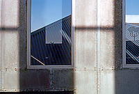 Frank Gehry: ICS/ERF Complex, Irvine. Within stair tower, looking through window to pitched roof of the metal-clad administration building.  Photo '86.