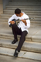 Guitar player on university steps.