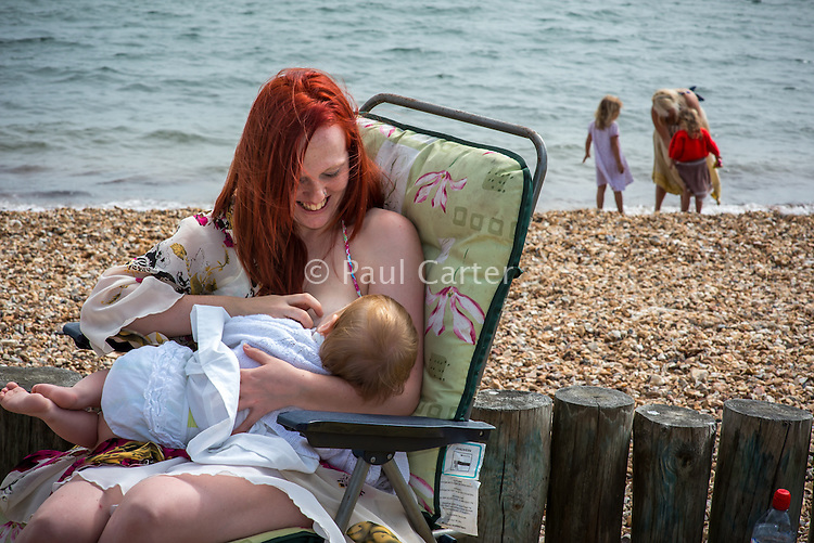 A young mother breastfeeding her baby while sitting in a folding  chair on the beach .<br /> <br /> Image from the breastfeeding collection of the &quot;We Do It In Public&quot; documentary photography picture library project: <br />  www.breastfeedinginpublic.co.uk<br /> <br /> <br /> Hampshire, England, UK<br /> 03 /09/2013<br /> <br /> &copy; Paul Carter / wdiip.co.uk