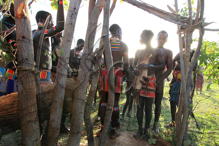 At the foot of the initiation door, a hive called a banzi will be the receptacle for the offerings made to procure prosperity and happiness for the young maza. The offerings will be pearl bracelets, headbands, milk and also honey, but above all the sculpted wood phallic symbol, the boko, for courage and virility. When the young man marries, a miniature hive will be set up with these same offerings on his hut's rooftop. ///Au pied de la porte d'initiation, une ruche appelée banzi sera le réceptacle des offrandes qui seront faites pour souhaiter prospérité et bonheur au jeune maza. Il s'agit de bracelets de perles, de bandeaux, de lait mais aussi de miel et surtout du symbole phallique sculpté en bois, le boko, pour le courage et la virilité. Lorsque le jeune se mariera, une ruche miniature sera installée avec ces mêmes offrandes au faîte de la charpente de la case.