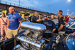 Bellmore, New York, USA. 12th June 2015. A massive BDS blower sticks through the hood opening in a blue modified 1963 Plymouth, with people walking and talking, at the Friday Night Car Show held at the Bellmore Long Island Railroad Station Parking Lot. Hundreds of classic, antique, and custom cars were on view at the free weekly show, sponsored by the Chamber of Commerce of the Bellmores.