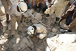 Syrian rescue workers remove a body from under the rubble following a reported barrel-bomb attack by Syrian government forces, in the Tariq al-Bab neighbourhood in the northern city of Aleppo, on August 21, 2015. Photo by Ameer al-Halbi