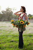 USA, California, Sonoma, Les Petit Maisons guest cottages and Market, owner Gayle Jenkins walks with freshly cut sunflowers
