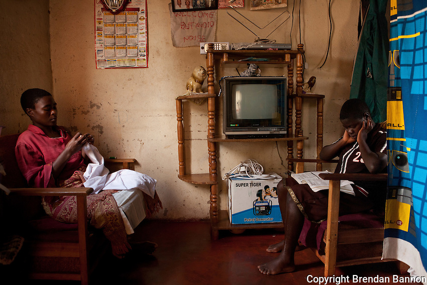 """Cynthia and her daughter Vimbai relax at home. Vimbai, although not in school due to economic hardship is reviewing her old school notes. Cynthia Yelulani is the mother of Vimbai  Chitani (15). Both are enrolled in the MSF HIV/AIDS project in Epworth, an urban settlement adjacent to the capital Harare of Zimbabwe. """"In 2007 Vimbai and I were both tested as Vimbai was feeling very sick. We were enrolled in the programme and we are now both much better. My biggest worry now is that I may have to send Vimbai to my mother in the countryside as I don't have enough money to pay for her school here. I still have to find out if there is a good HIV/AIDS project there."""".With 14.3 per cent prevalence rate (UNAIDS 2009), Zimbabwe is one of the countries worst affected by the worldwide HIV/AIDS epidemic. Since 2007, MSF has been running an HIV/AIDS project in Epworth. In August 2011, MSF had 12,864 patients under care in both of its clinics there."""