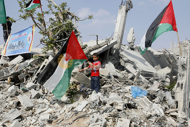 A Palestinian boy holds his national flag during the visit of Prime Minister Rami Hamdallah to the Beit Hanoun in the northern Gaza Strip on October 9, 2014. The Palestinian unity government which took the oath of office in June under technocrat prime minister Rami Hamdallah arrived to Gaza Strip on Thursday to convene the first fully meeting. Hamdallah said that the unity government will rebuild the bombed-out Gaza Strip following a seven-week Israeli offensive. Photo by Abed Rahim Khatib