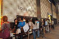 People queuing up to get into a Louis Vuitton flagship store in Central, Hong Kong. Louis Vuitton step up the battle for a bigger slice of the Asian market with the re-opening of its massive store after a year of renovation - more than double the size of its old shop..