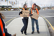 "Beth Brockman, left, and a large group of ministers and supporters join panhandler Carl Bittner, right, and other solicitors on Monday, March 25, to protest Durham's new ordinance outlawing the practice on ""busy streets."" Bittner was surprised to find Brockman and others at his usual intersection of 15-501 and Mt. Moriah Road, but was glad to have their company and ""good looks"" as he joked with them about the lessons they had yet to learn about panhandling. Officers from the Durham Police Department arrived and dispersed informational sheets about the new ordinance then left the intersection."